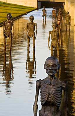 "Jens Galschiøt's copper statues of starving African men are displayed wading in the water pond that surrounds the Bella Center, venue for the COP15 summit in Copenhagen. Galschiøt titled his sculpture installation, ""The Pulse of the Earth."" Photo by Jo@kimlarsen.eu/SevenMeters.Net"