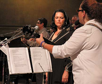 Mayra Bermudez listens to fellow ensemble member Clara Alvear play the cuatro. Photograph by Mark Vallen ©.