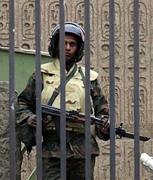 A soldier cradling an AK-47 automatic rifle with a fixed bayonet, stands behind the locked gates of the Egyptian Museum. AP Photo.