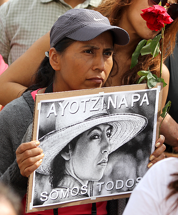 "On March 22, 2015, thousands of Angelenos joined relatives of the Ayotzinapa 43 in a protest march on the Mexican Consulate in Los Angeles. In this photo one of the marchers holds the poster, ""We Are All Ayotzinapa."" Photo/Mark Vallen ©"