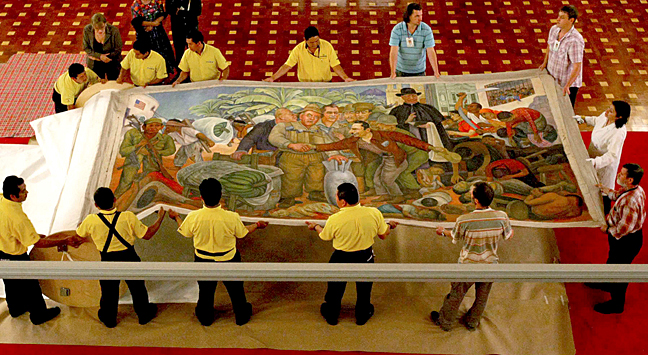 "Museum staff from Guatemala's National Palace of Culture, and experts from Russia's Puskin Museum, uncrate Rivera's painting in preparation for the exhibit ""Oh Revolution! 1944-2010 Multiple Visions,"" held in Guatemala's capital in 2010. Photo by Paulo Raquec for the Government of Guatemala."