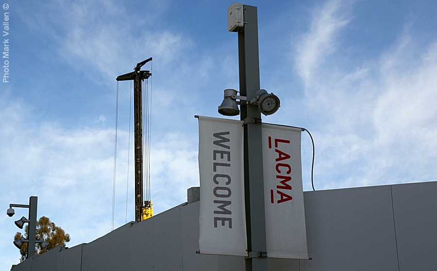 """LACMA Idyll."" A formidable grey security wall some 15 ft tall, encircles what is left of museum grounds. The barrier completely forbids the public a view of ongoing construction. An incongruous ""welcome"" sign cloaks a drab tableau of destruction. Photo Mark Vallen ©. Feb 14 2021."