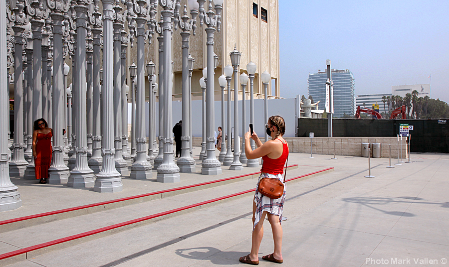 """Selfies."" In the background you can see wrecking cranes and tractors pulverizing LACMA into dust, as people take selfies at the Urban Light ""sculpture."" Photo Mark Vallen ©. May 13, 2020"