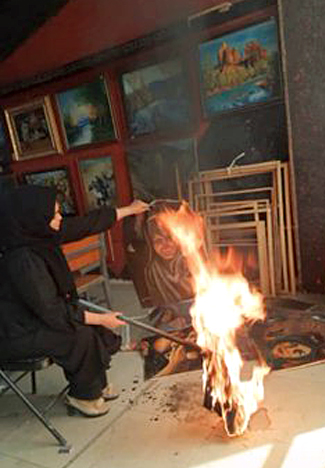 An unidentified artist in Kabul burns her paintings before the Taliban discovers her studio. Photo: Omaid Sharifi 2021